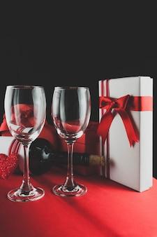 白ギフトと2つの空のグラスで横たわってワインのボトル