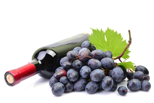 ブドウのクローズアップの横にあるワインのボトル