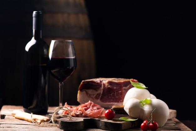 소박한 전통 이탈리아 음식과 함께 테이블에 유리잔을 얹은 와인 한 병.신선한 이탈리아 생활 방식