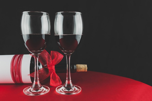赤いリボンとワインのボトルとワイングラス2杯