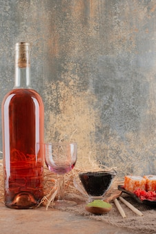 Бутылка вина с рюмкой и суши на мешковине