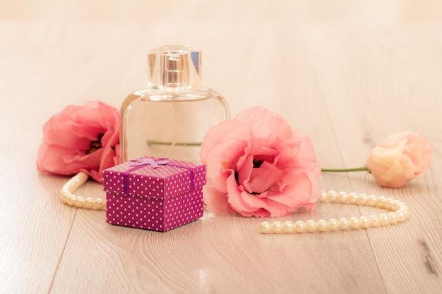 분홍색 배경에 선물 상자와 꽃이 있는 여성 향수 한 병. 휴일 개념