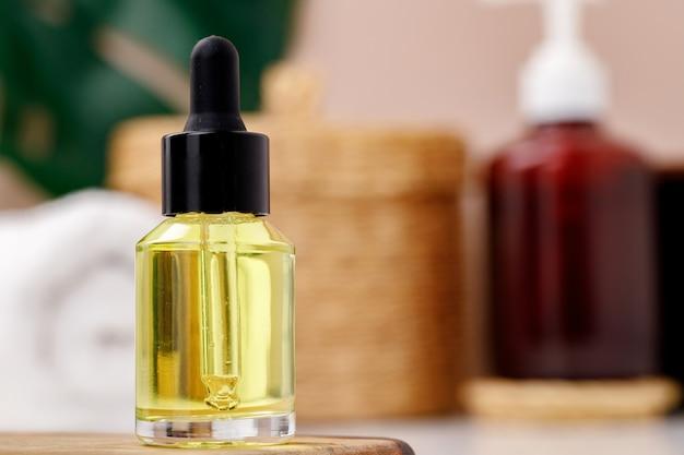 Бутылка желтого косметического масла на деревянном подносе крупным планом фото