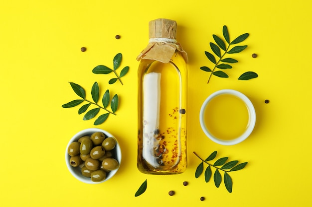 Bottle of oil, olives, twigs and pepper on yellow