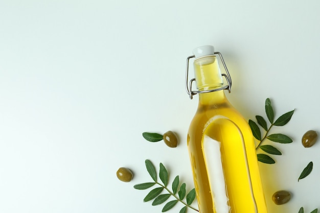 Bottle of oil, olives and twigs on white surface