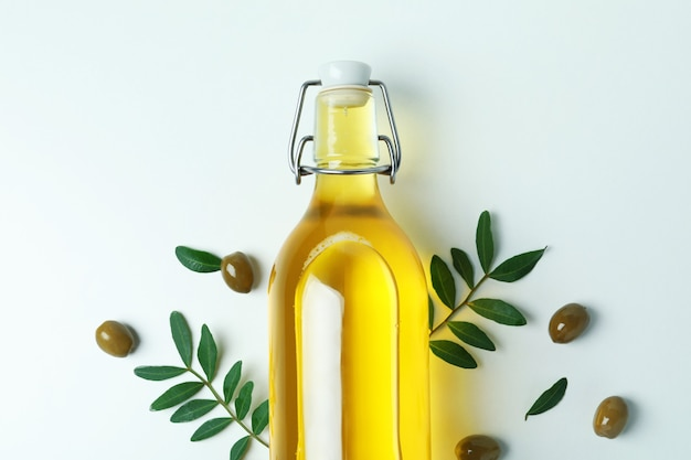 Bottle of oil, olives and twigs on white