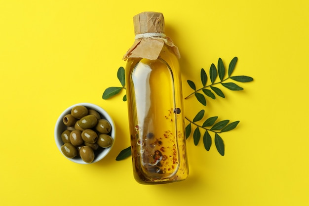 Bottle of oil, olives and twigs on yellow surface