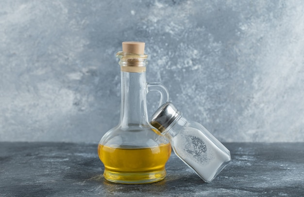 Bottle of oil and salt on grey background.