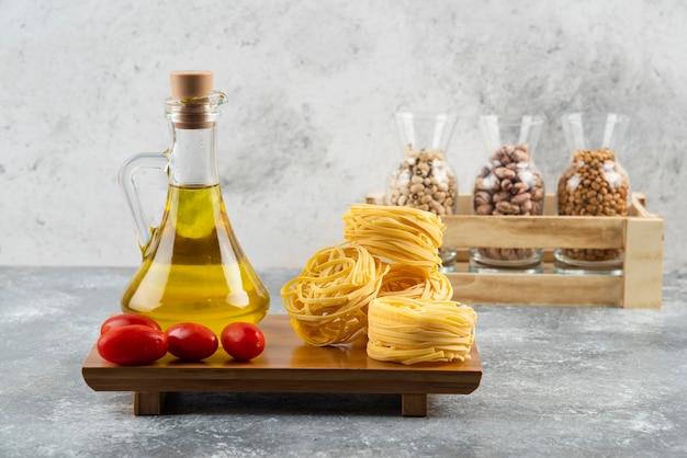 Una bottiglia di olio con pasta nido cruda e pomodorini.