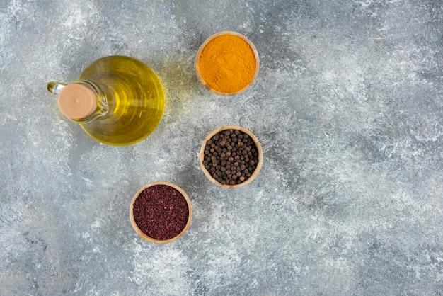 Una bottiglia di olio con ciotole di legno di peperoni.