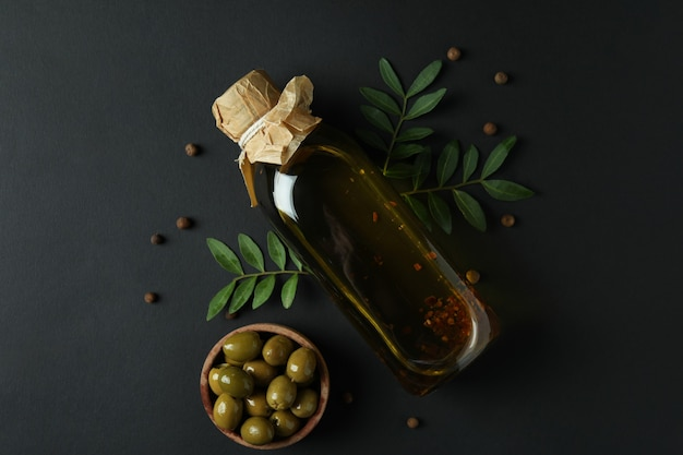 Bottle of olive oil, bowl of olives, twigs and pepper on black surface