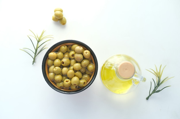 Bottle of olive oil and fresh olive in a container on white