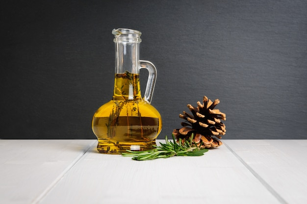 Bottle of olive oil, fresh rosemary branch and pine cone on white wooden table