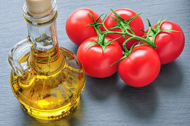 Bottle of olive oil with herbs and red tomatoes