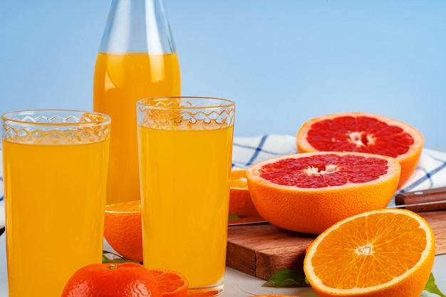 Bottle of orange juice and fresh oranges on table