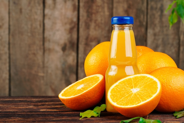 Bottle of orange juice with oranges on wooden table