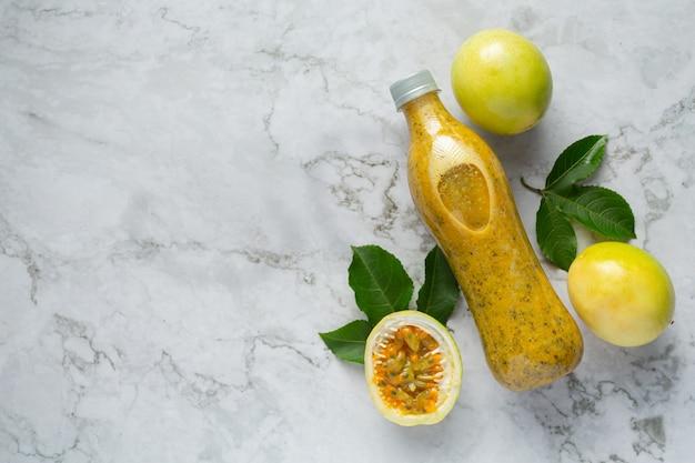 Una bottiglia di succo di frutto della passione e frutto della passione fresco tagliato a metà sul pavimento di marmo bianco