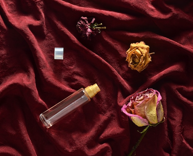A bottle of perfume and buds of dried roses on a red silk. romantic look. top view.