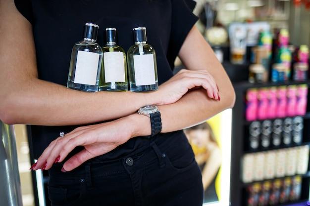 ボトル香水女性の手。香水のボトルを保持している若い女性。女性の手にファッショナブルな香水。女の子は香水をスプレーします。美しい女性の手。