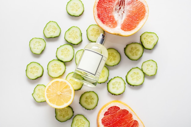 A bottle for perfume or fragrance oil, against a wall of fresh cucumbers and citrus fruits including lemon and grapefruit. concept ingredients of fresh aromas, aromatherapy.
