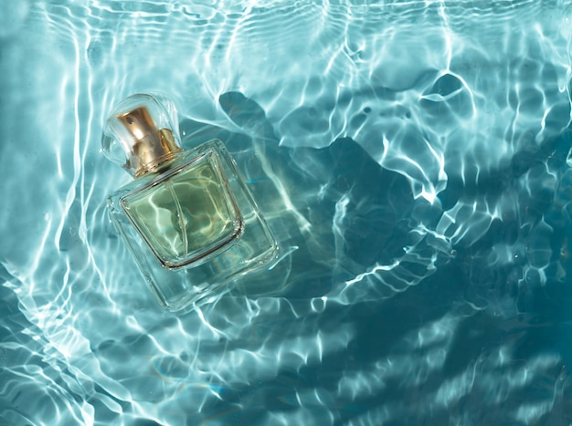 Флакон духов в голубой воде с тенями вид сверху и копией пространства