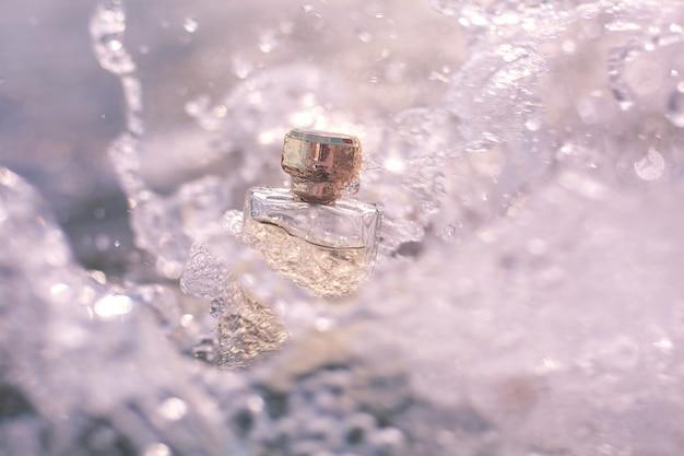 Bottle of perfume in sea foam
