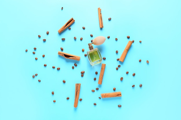 Bottle of perfume with cinnamon and coffee beans on color background