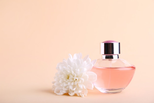 Bottle of perfume with flower on beige