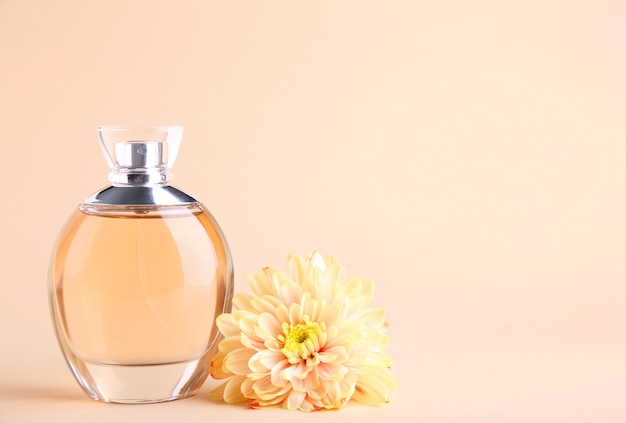 Bottle of perfume with flowers on beige