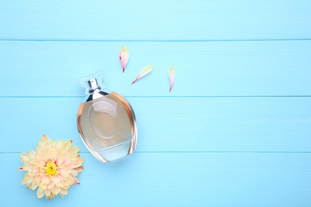 Bottle of perfume with flowers on blue background