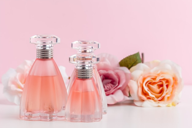 Bottle of perfume with flowers on color