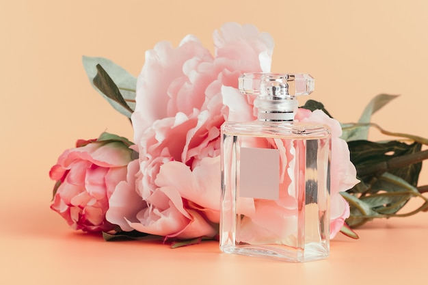 Bottle of perfume with flowers on light cloth