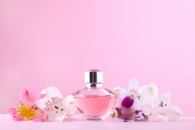 Bottle of perfume with flowers on pink
