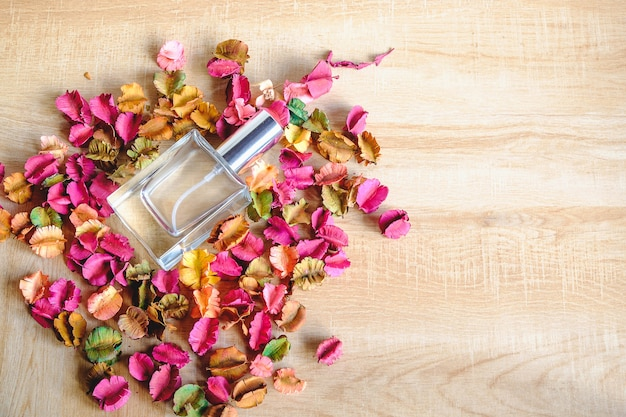 Bottle of perfume with flowers on wood background
