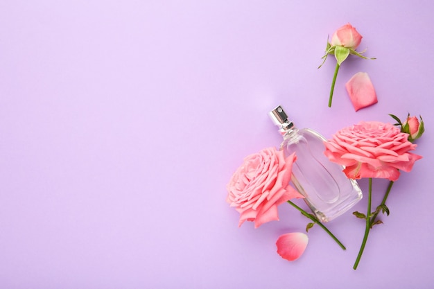 Bottle of perfume with pink roses on violet.