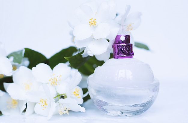 Bottle of perfume with scent of flowers on white surface
