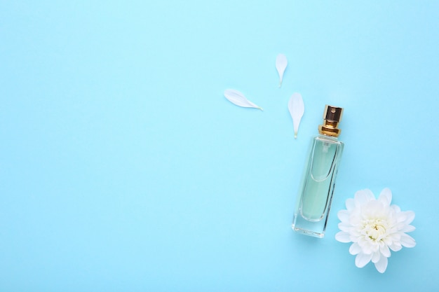 Bottle of perfume with white flower on blue background