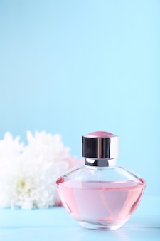Bottle of perfume with white flowers on blue