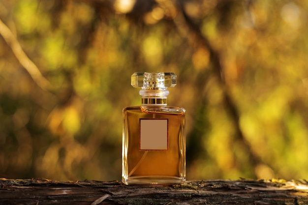 Bottle of perfume on yellow nature background