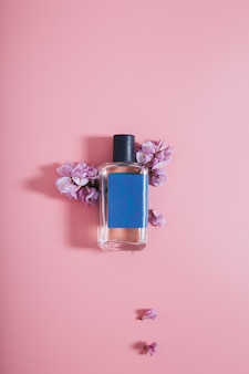 Bottle of perfumes on pink wall with flowers