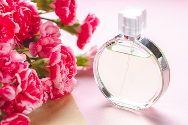 A bottle of person perfume and a bouquet of flowers on a pink surfce. give presents and flowers to person. receive gifts from loved people on holidays