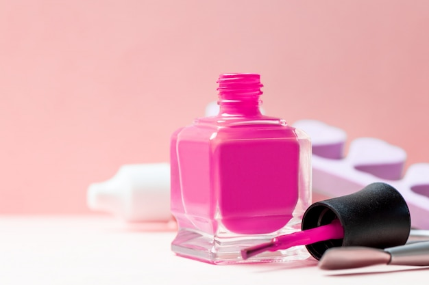 Bottle of pink nail polish and manicure tools on a table.