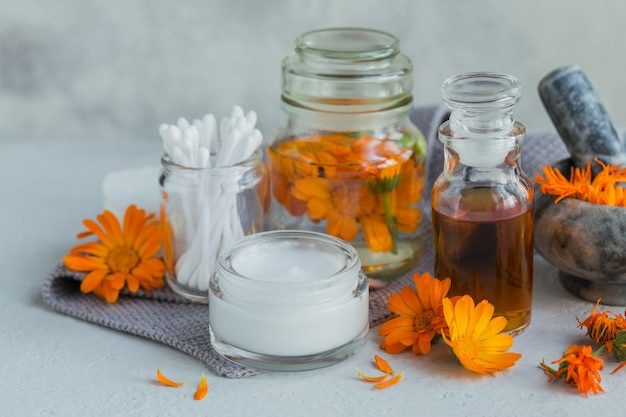 A bottle of pot marigold tincture or infusion, ointment, cream or balm with fresh and dry calendula flowers and cotton pad and sticks on white.