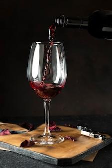 검은 배경에 유리에 레드 와인을 붓는 병