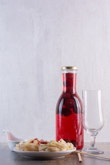 Bottle of red juice with empty glass and pasta on white surface
