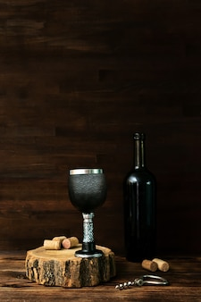 Bottle of red wine and black glass, corkscrew and corks on wooden table, dark alcohol beverage drink background, still life.