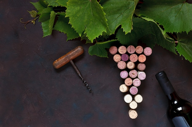 A bottle of red wine, corks, corkscrew and grape leaves.