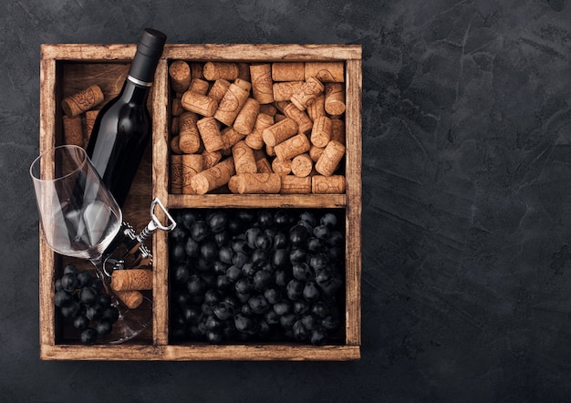 Bottle of red wine, corks and grapes in a wooden box