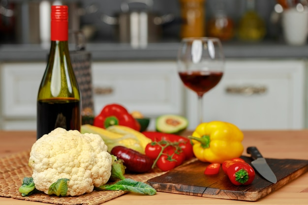 Bottle of red wine and fresh vegetables on kitchen table