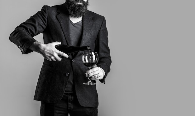 Бутылка, бокал для красного вина. бородатый мужчина, бородач, сомелье, дегустация. переливание красного вина из бутылки в рюмку. официант наливает красное вино в бокал. черное и белое.